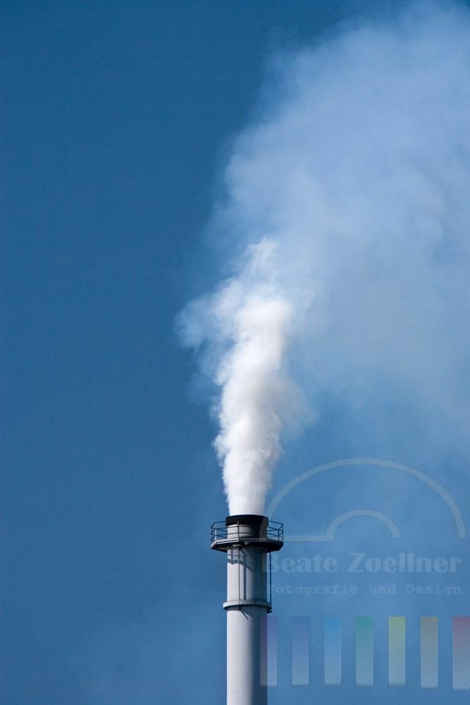Industrie-Schornstein bläst weisse Emissionswolke in den blauen Himmel