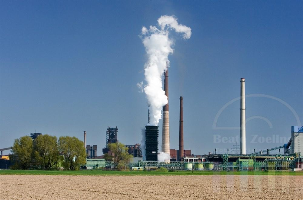 Schwerindustrie mit rauchenden Schloten im Hintergrund, frisch bestellte Äcker und Felder im Vordergrund, blauer Himmel