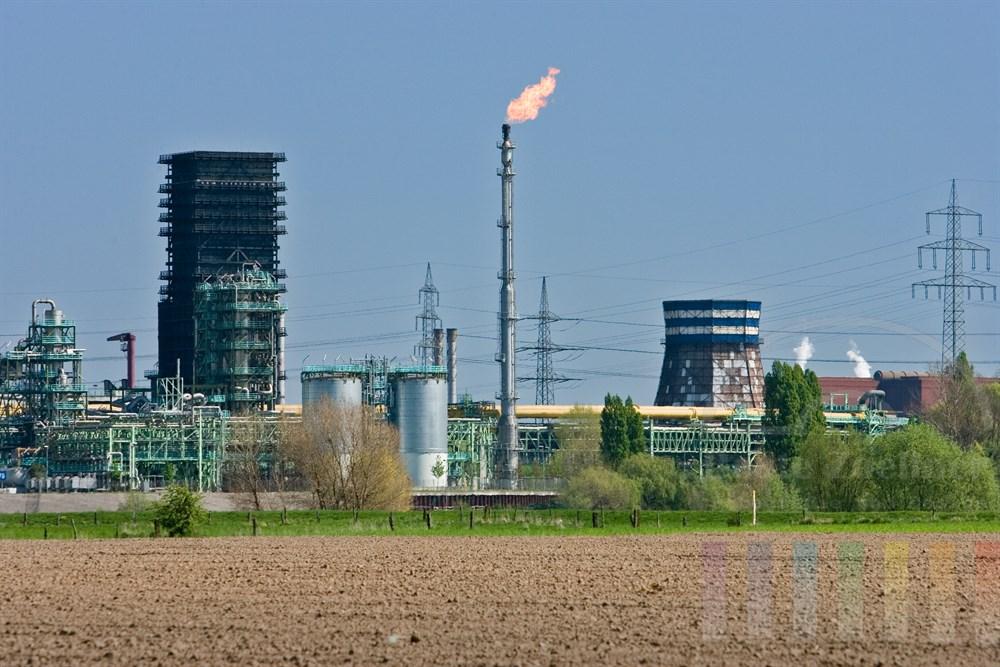Stahlwerk in Duisburg, über einen Schronstein wird überschüssiges Gas abgefackelt. Im Vordergrund ein frisch bestellter Acker