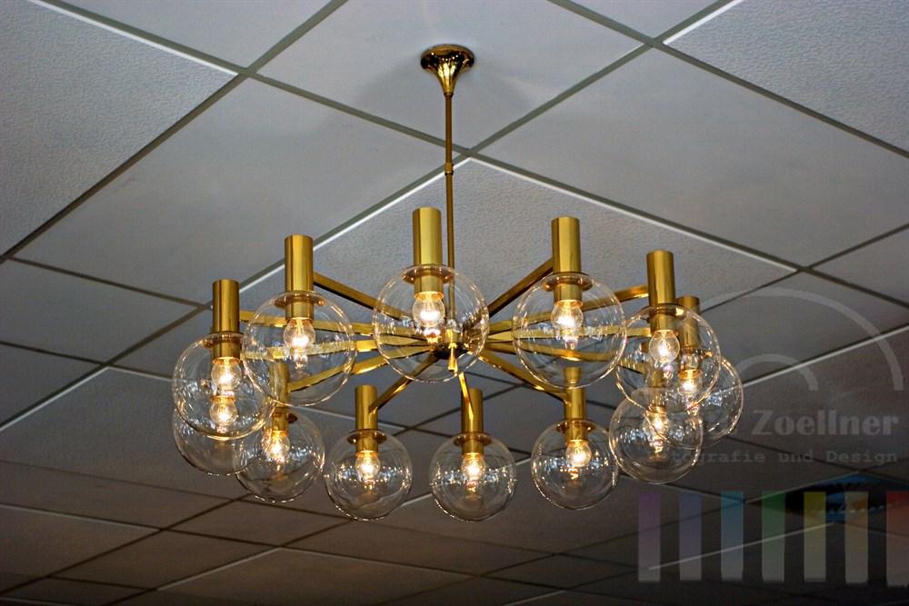 messingfarbene Lampe mit Glaskugeln hängt von der Decke eines Speisesaals