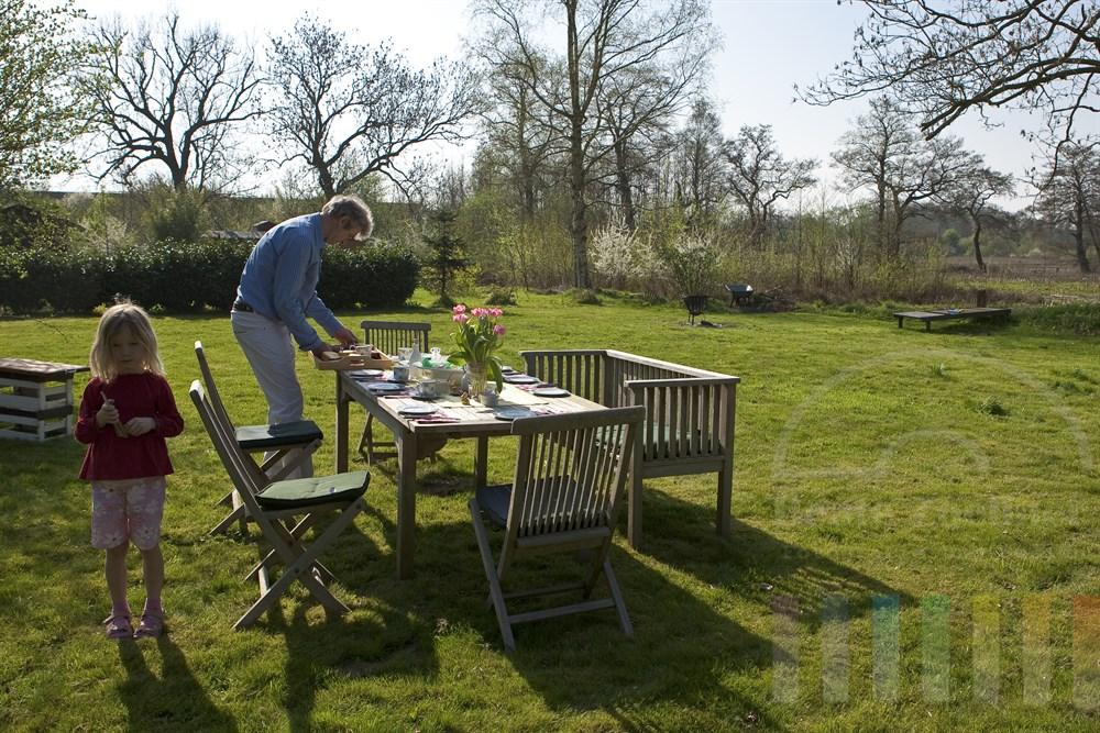 Mann deckt Tisch im Garten für ein Osterfrühstück im Freien