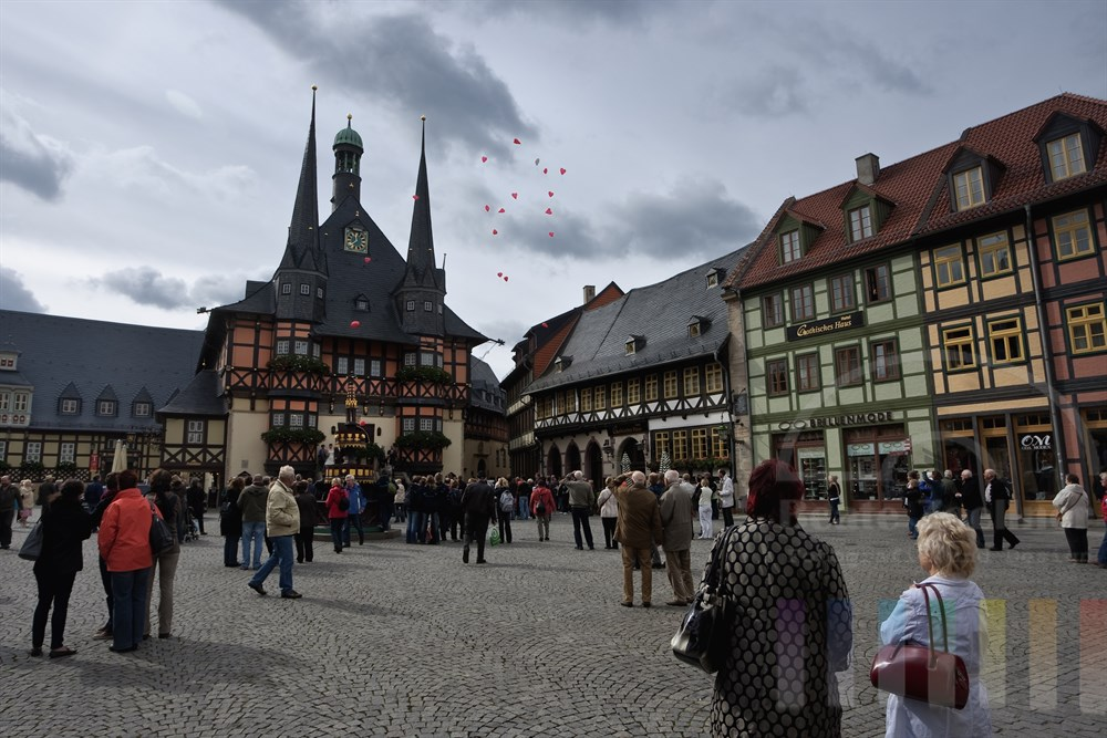 Rathaus und Marktplatz in Wernigerode - im Rathaus hat gerade eine Trauung stattgefunden. Zahlreiche rote Luftballons in Herzform steigen in den Wolkenhimmel auf, Passanten und Touristen schauen zu