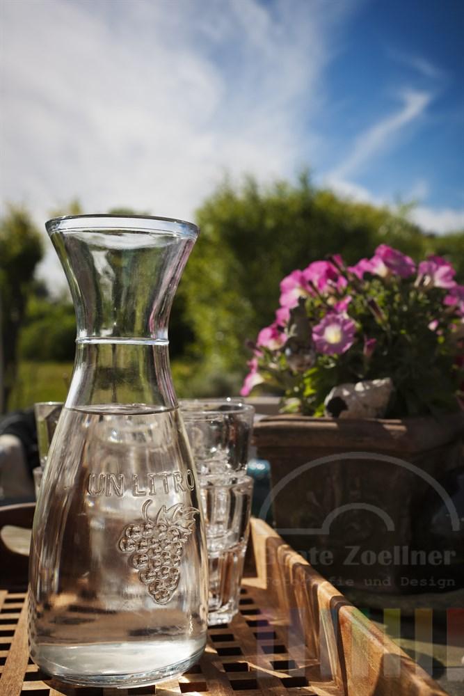 Karaffe mit Wasser auf Holz-Tablett im Garten unter blauem Himmel