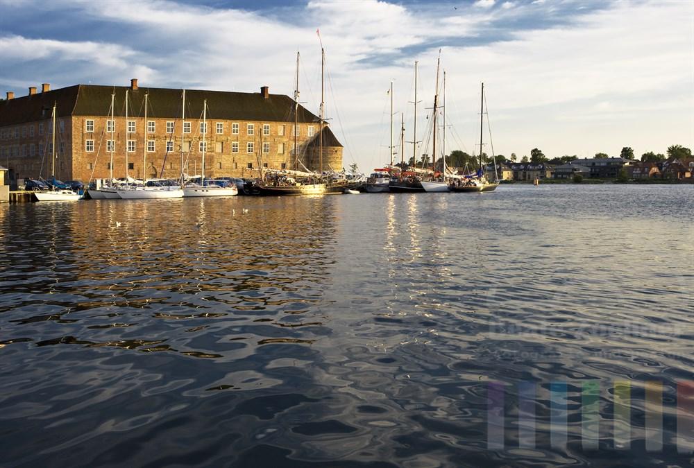 Abendstimmung im Stadthafen von Sonderburg (Dänemark) - zahlreiche Segelyachten und Traditionssegler liegen am Ufer vor dem historischen Schloss der Stadt