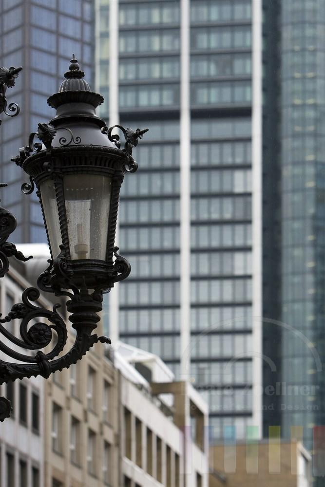 historische Straßenlaterne vor moderner Hochhausfassade in Frankfurt am Main