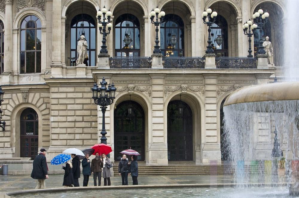 Touristen mit Regenschirmen stehen vor der Alten Oper in Frankfurt am Main