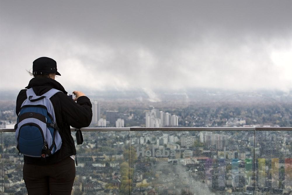 Touristin mit Rucksack und Muetze (rueckansicht)  steht auf dem Frankfurter Maintower und versucht - trotz Regenwetter und tief haengenden Wolken - ein Foto der Aussicht auf die Stadt mit ihrer Digitalkamera machen