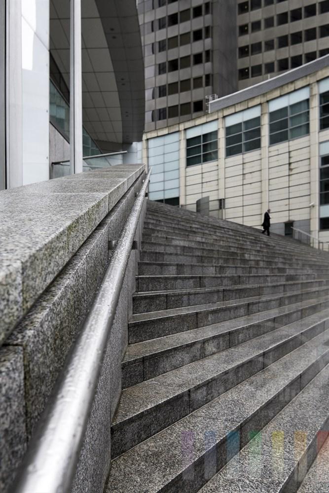 Fassaden und Treppe aus Stein, Glas, Beton und Stahl dominieren das Bild - nur ein einziger Mann hat sich in dieser harten, kalten Welt verirrt und versucht, ihr zu entkommen