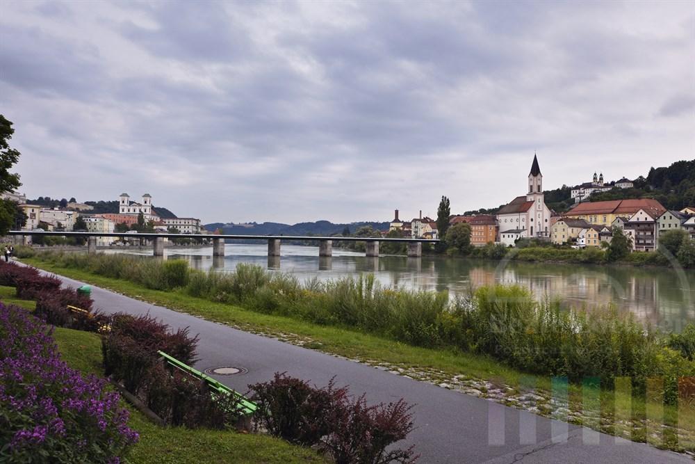 Blick ueber Gruenanlagen an  der Passauer Altstadt auf das gegenueber liegende Inn-Ufer, bewoelkt