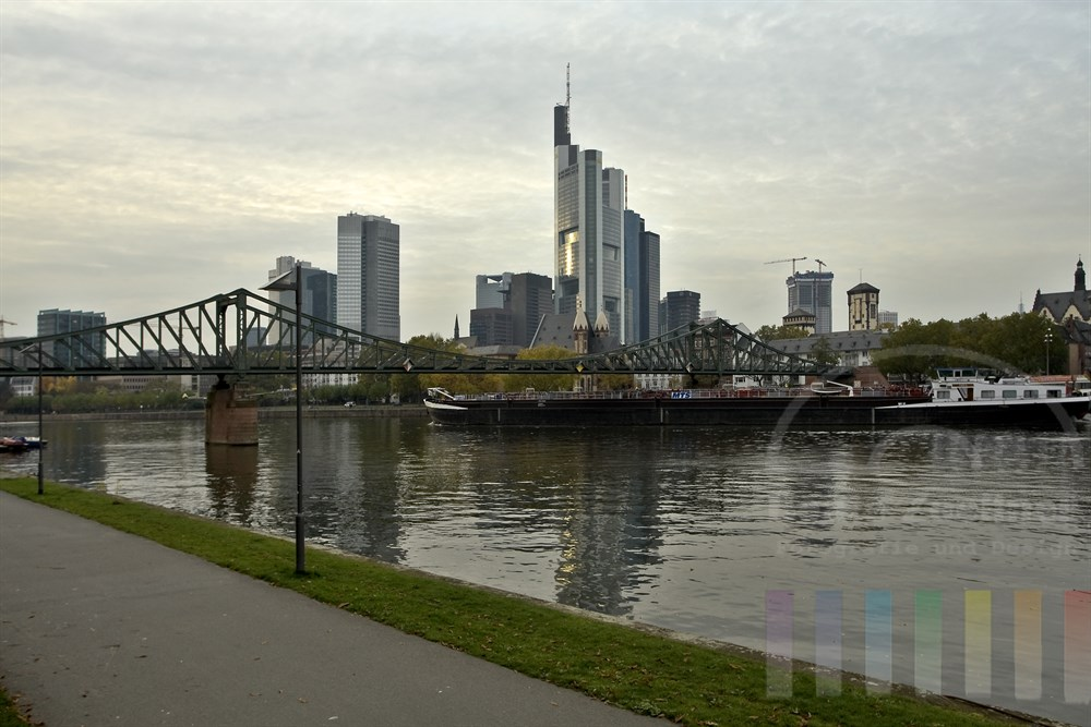 """Binnenschiff passiert auf dem Main die Skyline von Frankfurt. Der Bug schiebt sich unter die historische Fußgängerbrücke """"Eisener Steg"""", bewölkter Himmel, Herbststimmung"""