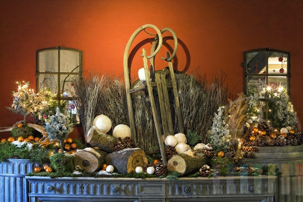 üppige Weihnachtsdekoration im Landhausstil auf einer Kommode, Innenaufnahme