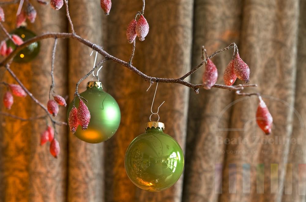 Weihnachtsdekoration: Grüne Glaskugeln hängen an einem mit Kunstschnee eingesprühtem Hagebutten-Zweig