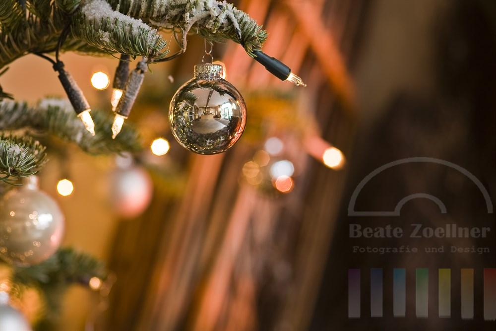 Weihnachtsdekoration: silberne Glaskugeln hängen an einem mit Kunstschnee besprühtem Tannenbaum. Eine Lichterkette beleuchtet die Deko