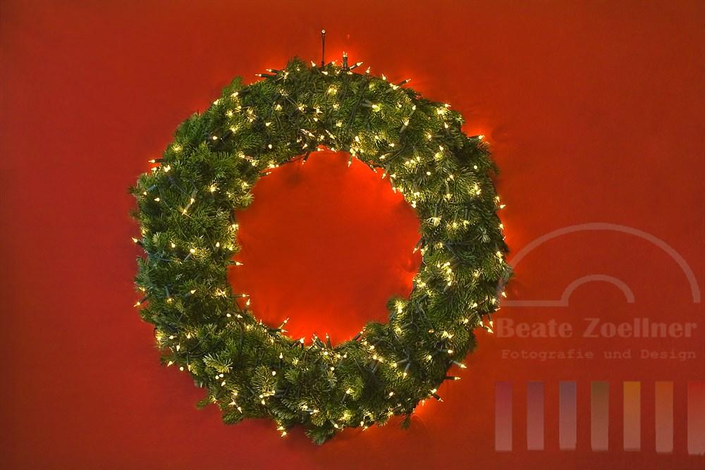 Mit Mini-Elektro-Kerzen beleuchteter Kranz aus Tannengrün hängt an roter Wand