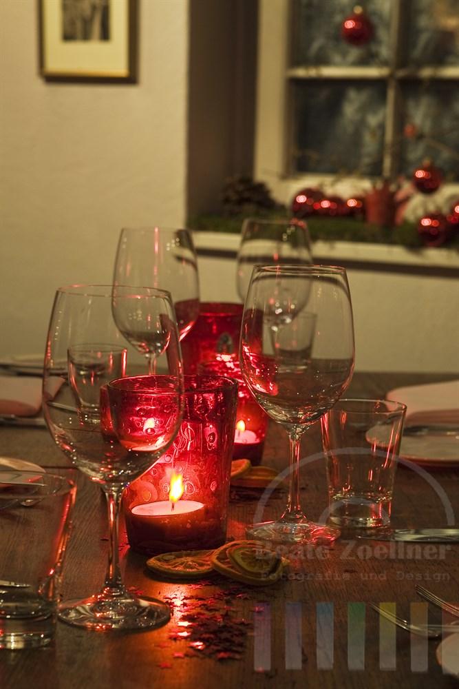 Weihnachtlich und im Landhaussstil dekorierter Holzisch mit Gläsern und Kerzen