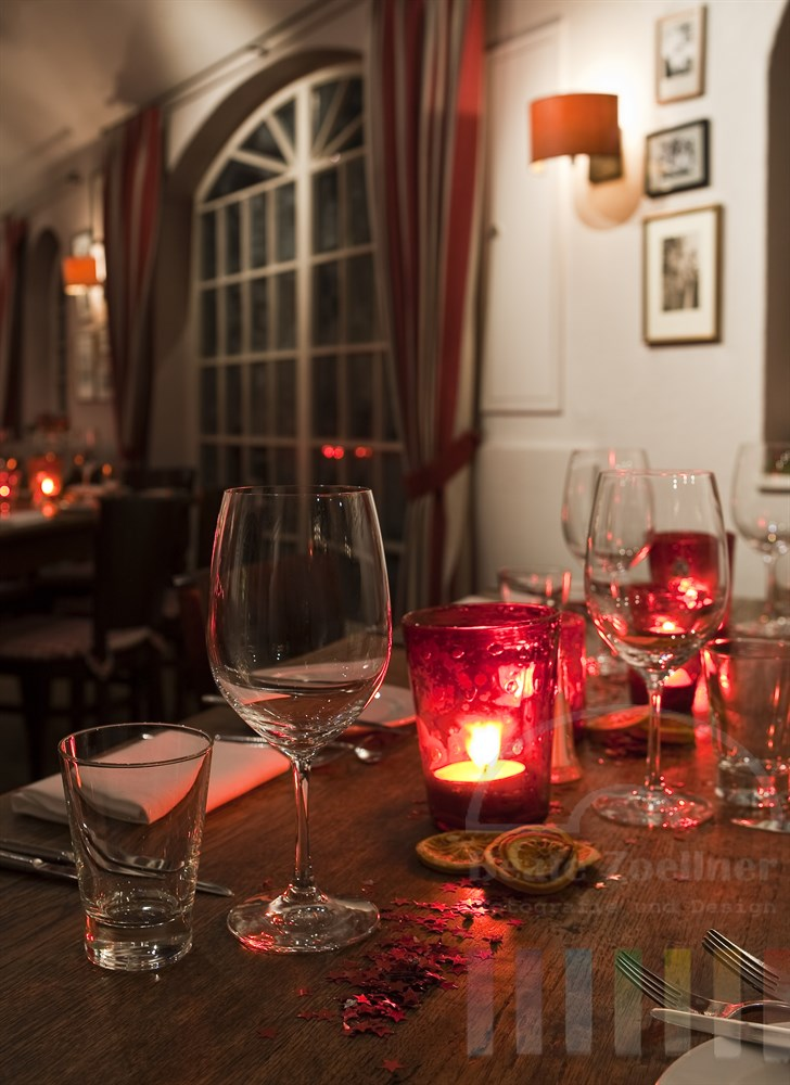 Weihnachtlich und im Landhaussstil dekorierte Holztische mit Gläsern und Kerzen in einem Restaurant