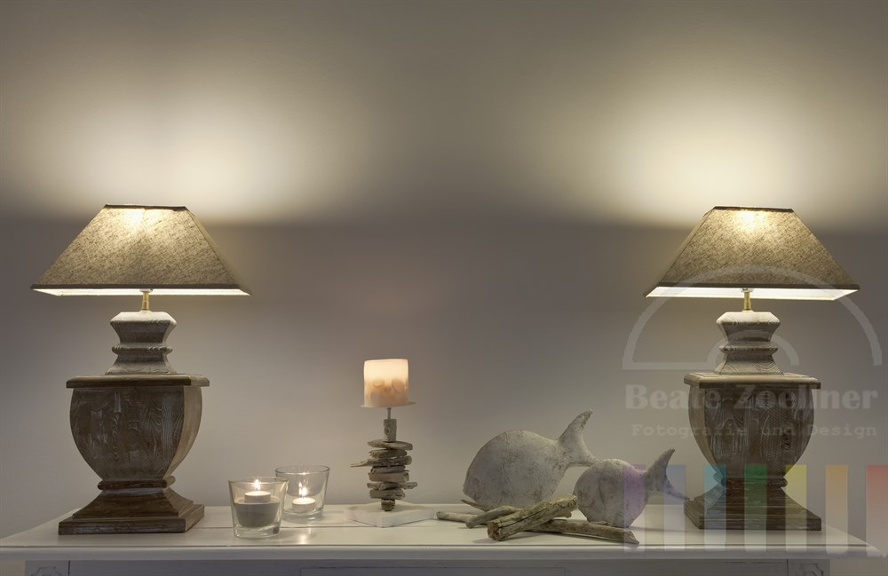 zwei Lampen stehen auf einem liebevoll dekorierten weißen Holztisch und werfen ihren Lichtschein auf die weiße Wand dahinter