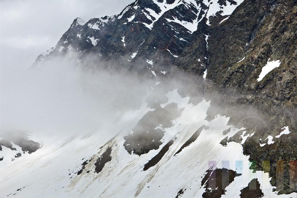 Sonnenlicht dringt durch Wolkenschleier auf eine schroffe Felswand mit Schneefeldern im Hochgebirge am Timmelsjoch