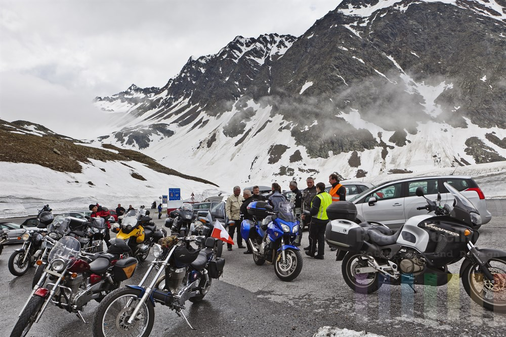 Gruppe von Motorradfahrern pausiert auf der Passhöhe des Timmelsjochs (Grenze zwischen Österreich und Italien) in 2474m Hoehe