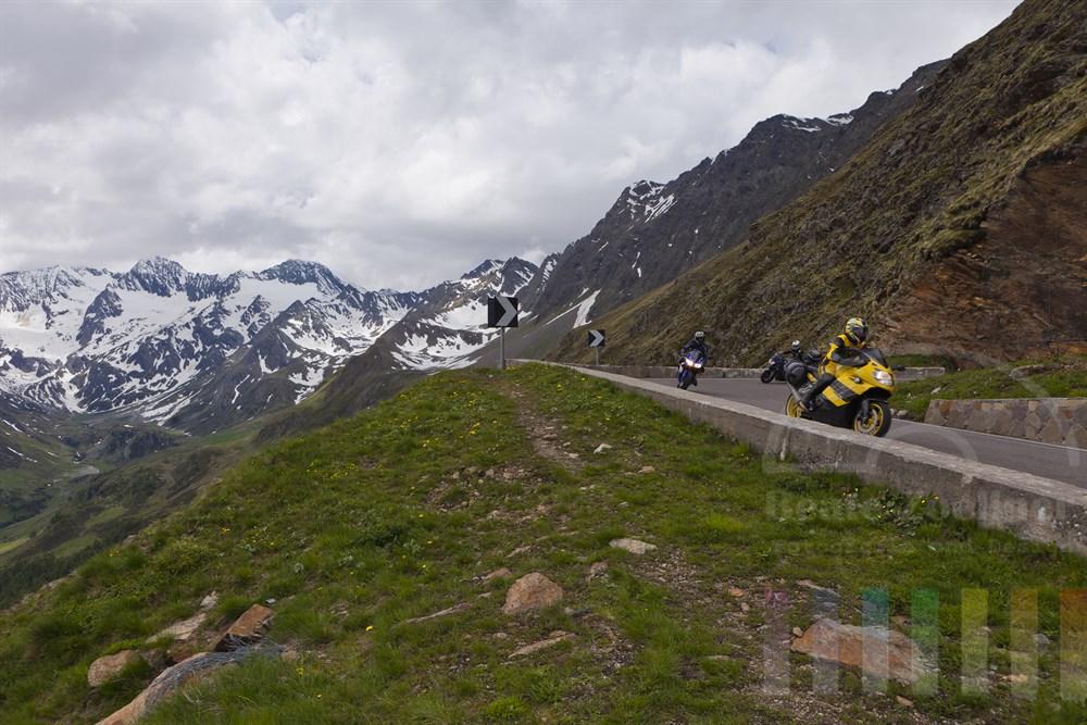 Gruppe von Motorradfahrern faehrt die Serpentinen auf der italienischen Seite des Timmelsjochs, Fruehsommer