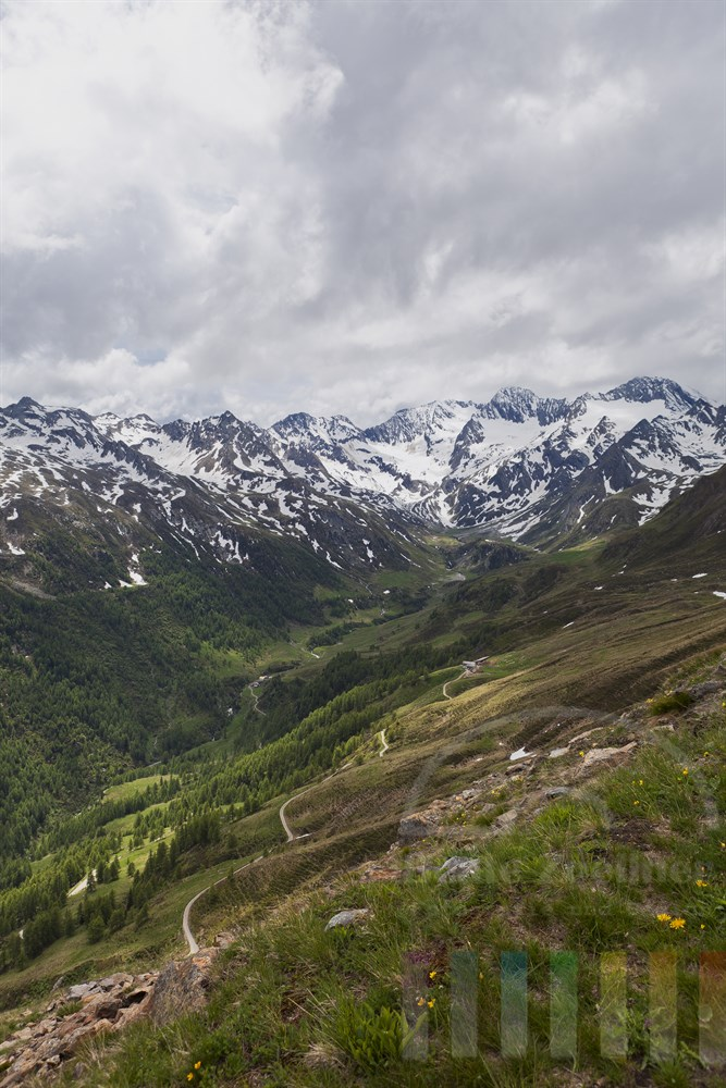 Blick von der Suedtiroler Seite der Timmelsjoch-Passstrasse auf ein einsam gelegenes Tal und schneebedeckte Berge
