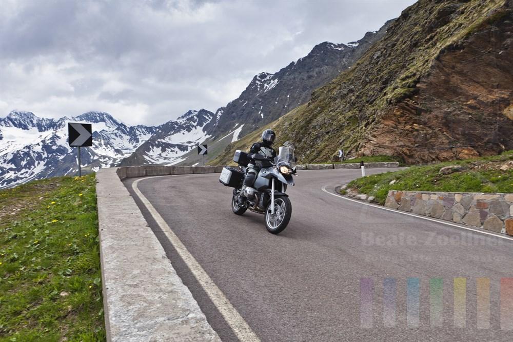 Mann auf Motorrad fährt durch die Serpentinen des Timmelsjochs bergab ins Passeiertal - im Hintergrund schneebedeckte Berggipfel