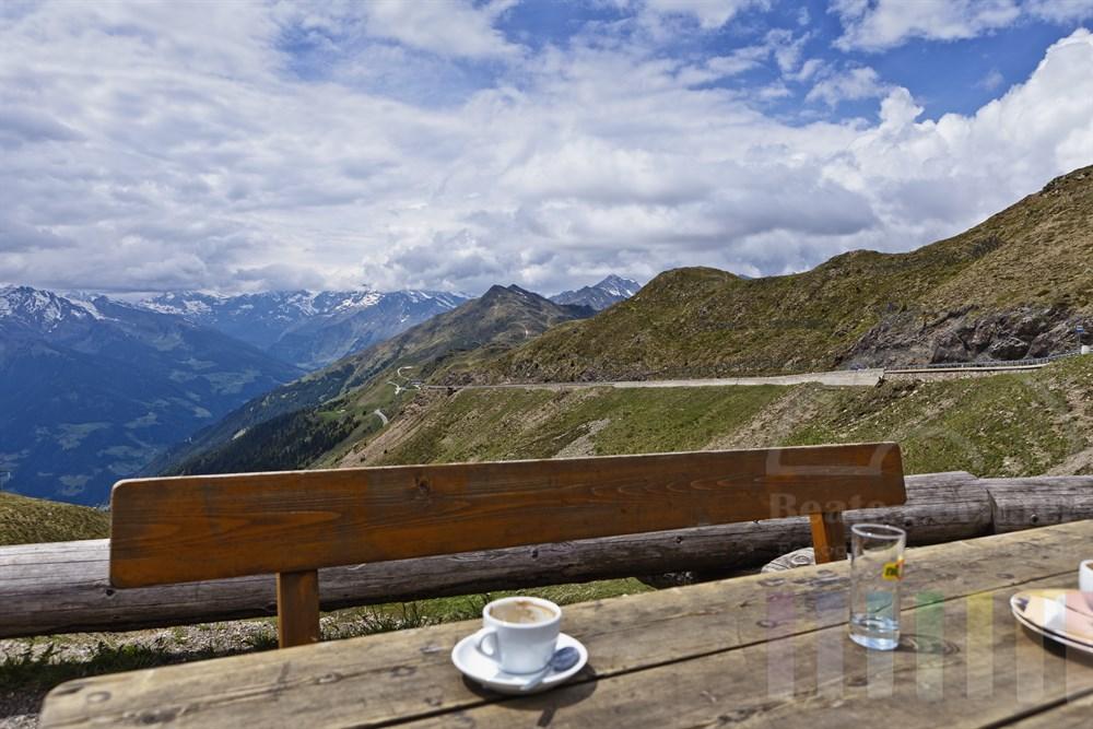 verlassener Holztisch mit Kaffeetassen auf der Terrasse der Edelweißhuette auf dem Jaufenpass in Suedtirol - Ausblick auf die Passstrasse und die Berge
