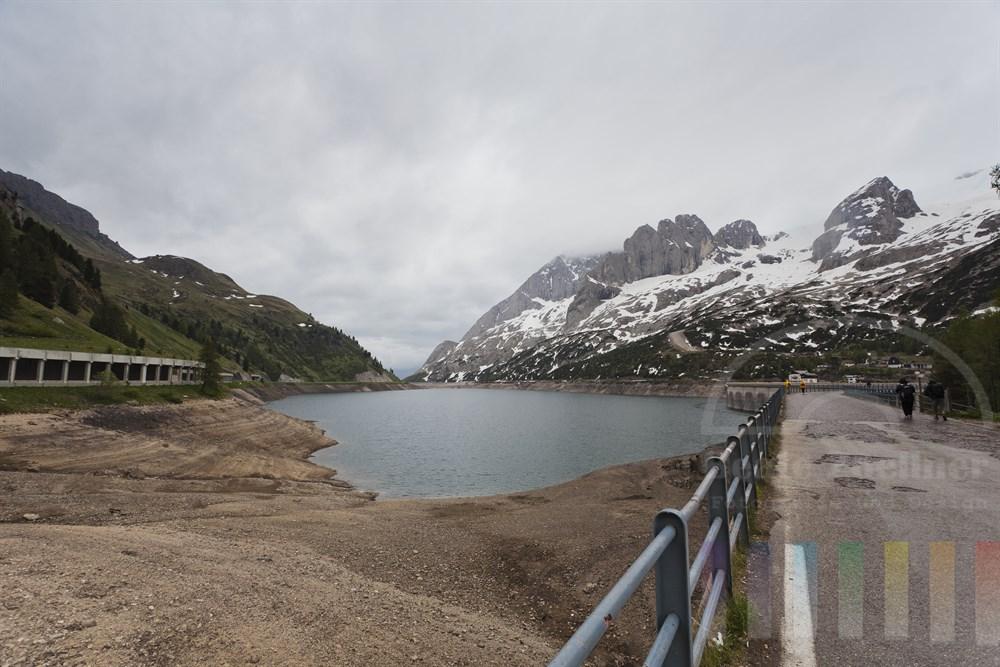 Blick vom Passo di Fedáia ueber den Stausee (bei sehr niedrigem Wasserstand) unterhalb des Marmolada-Massivs in Suedtirol, regnerisch