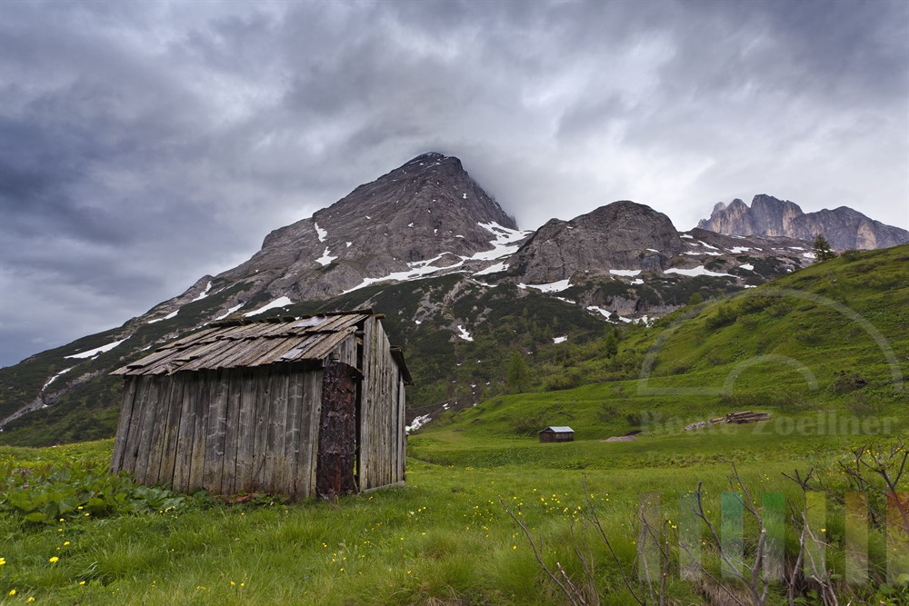 verfallene Almhuette in den Dolomiten vor Marmolada-Bergmassiv und wolkenverhangenem Himmel