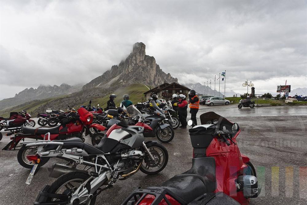 Motorradfahrer unterbrechen ihre Tour und pausieren im strömenden Regen am Passi Giau auf 2233 m Höhe