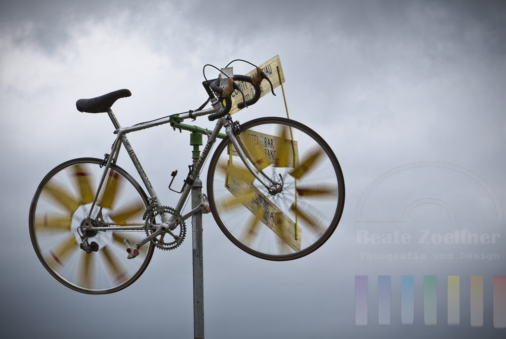 ausrangiertes Rennrad dient auf dem Passo Giau (2236m) in den Dolomiten aus Windanzeiger, dunkler Wolkenhimmel. Der Pass ist Rastplatz und Treffpunkt für zahlreiche, sportliche Radfahrer, die sich zuvor die Serpentinen der Passstrasse hoch gequaelt haben.