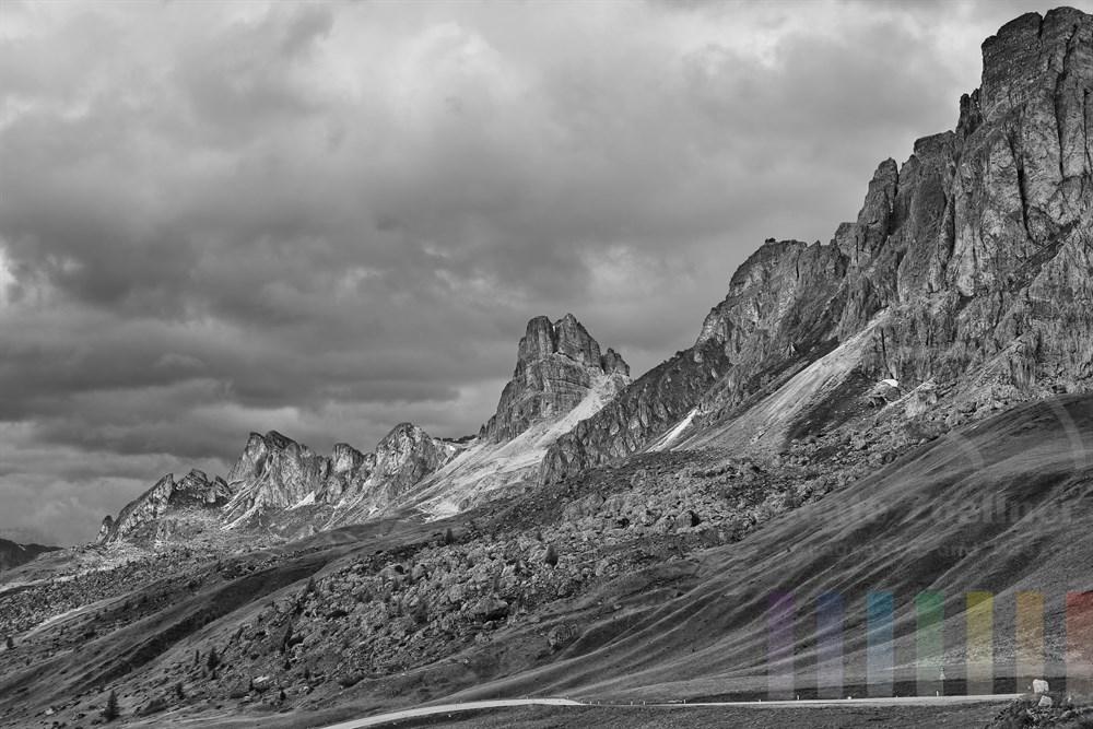 """Strasse zum Passo Giau (2233m) vor imposanten und für die Dolomiten typischen Felswaenden, die im Licht leuchten - Himmel bewoelkt. Ganz rechts die Felsnadel """"Ra Gusela"""""""