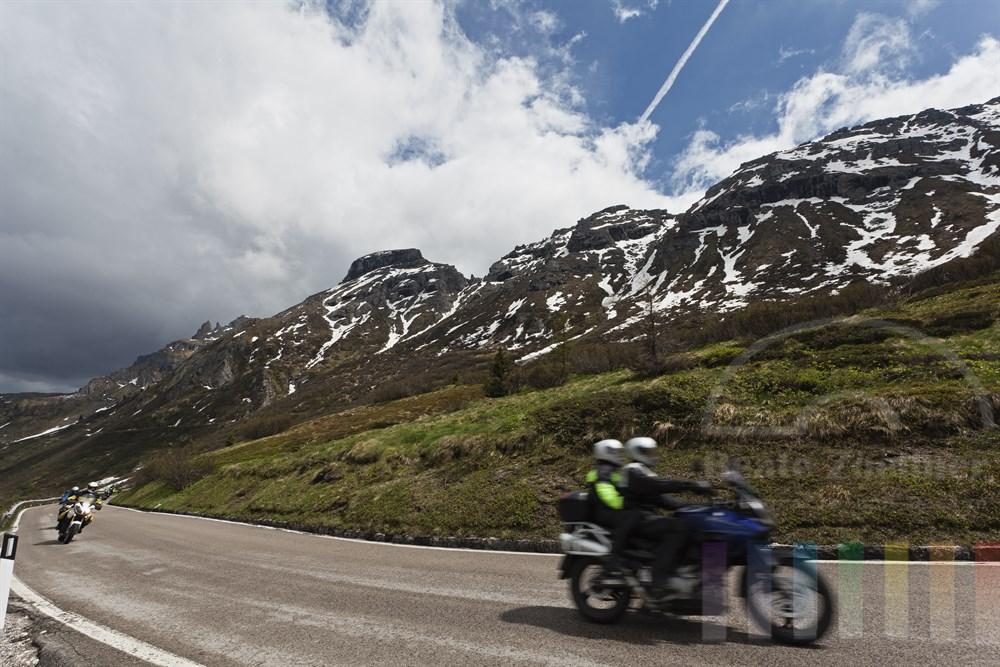 Gruppe von Motorradfahrern fahren auf der Passstrasse hinauf zum Passo Pordoi. Ihr Weg fuehrt sie an einer imposanten Bergkulisse entlang, sonnig