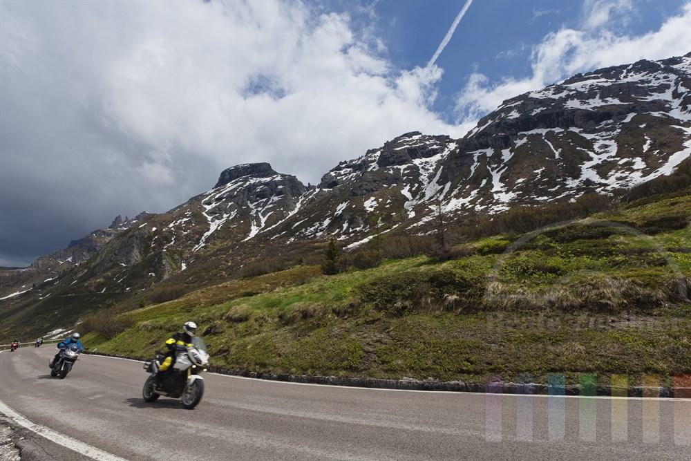Gruppe von Motorradfahrern faehrt vor Dolomiten-Kulisse zum Passo Pordoi (2239m) hinauf, sonnig, doch Regenwolken sind am Himmel