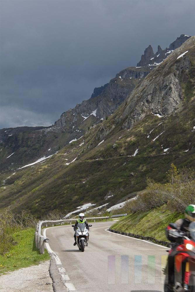 Zwei Motorradfahrer faehren vor Dolomiten-Kulisse zum Passo Pordoi (2239m) hinauf, sonnig, doch Regenwolken sind am Himmel