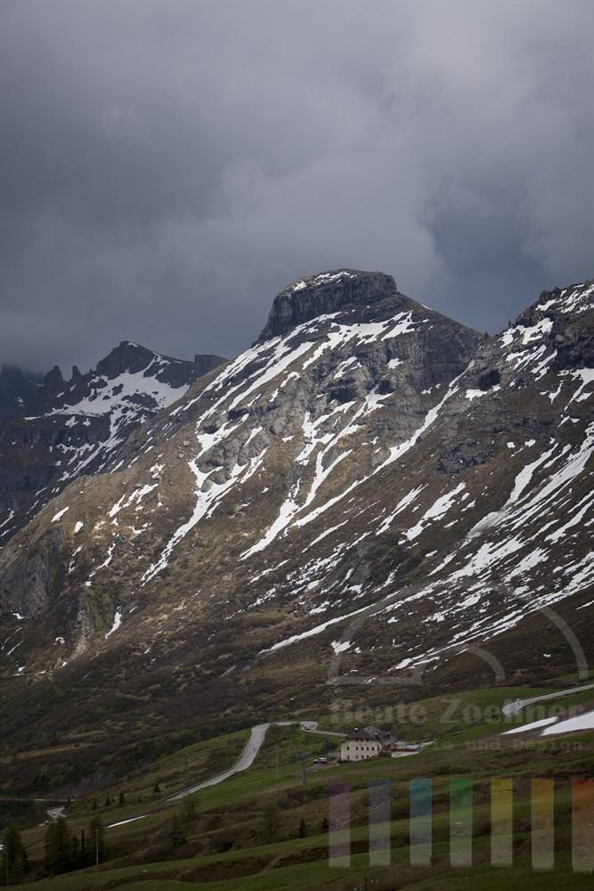 Die Sonne lässt eine Bergwand mit Schneefeldern in den Dolomiten erstrahlen, waehrend  am Himmel dunkle Regenwolken stehen und die Passstrasse zum Passo Pordoi hinauf im Schatten liegt