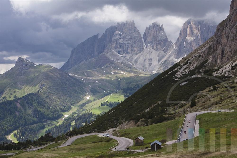 Blick vom Passo Pordoi (2239m) in den Dolomiten auf den Langkofel über dem Regenwolken stehen. Im Vordergrund bewegt sich der Verkehr durch die Serpentinen der Passstrasse Richtung Canazei