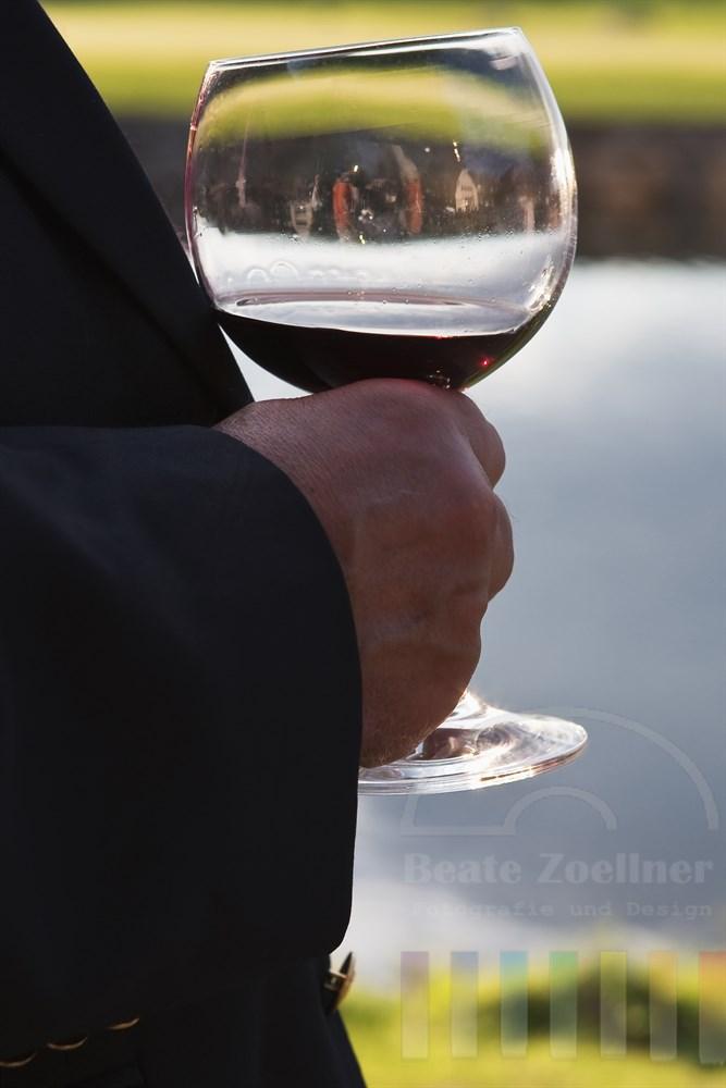 Mann haelt ein Glas Rotwein in der Hand - im Glas spiegelt sich die exklusive Location eines Golfhotels