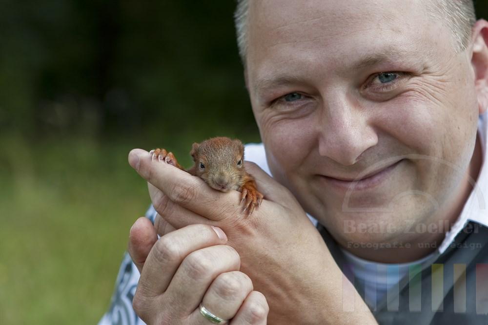 laechelnder Mann haelt liebevoll ein 5 Wochen altes Eichhoernchenbaby in seinen Haenden (geänderter Name des Mannes: Jan Eickhoff)