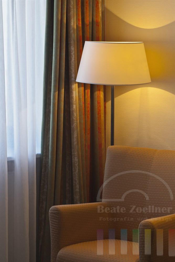 Sessel und Stehlampe am Fenster