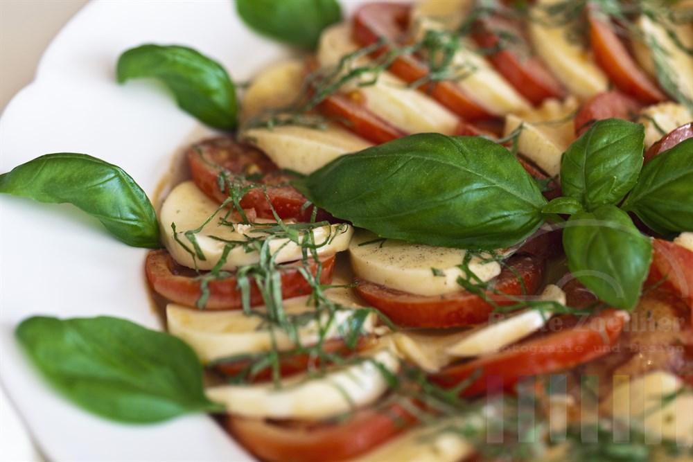 Tomate-Mozzarella mit Basilikum auf weißem Teller