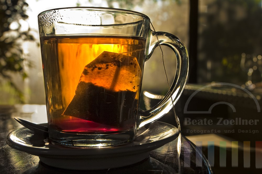 Glaeserne Tasse mit einem Aufgussbeutel Tee steht im Gegenlicht der Sonne auf einem Tisch in einem gastronomischen Betrieb