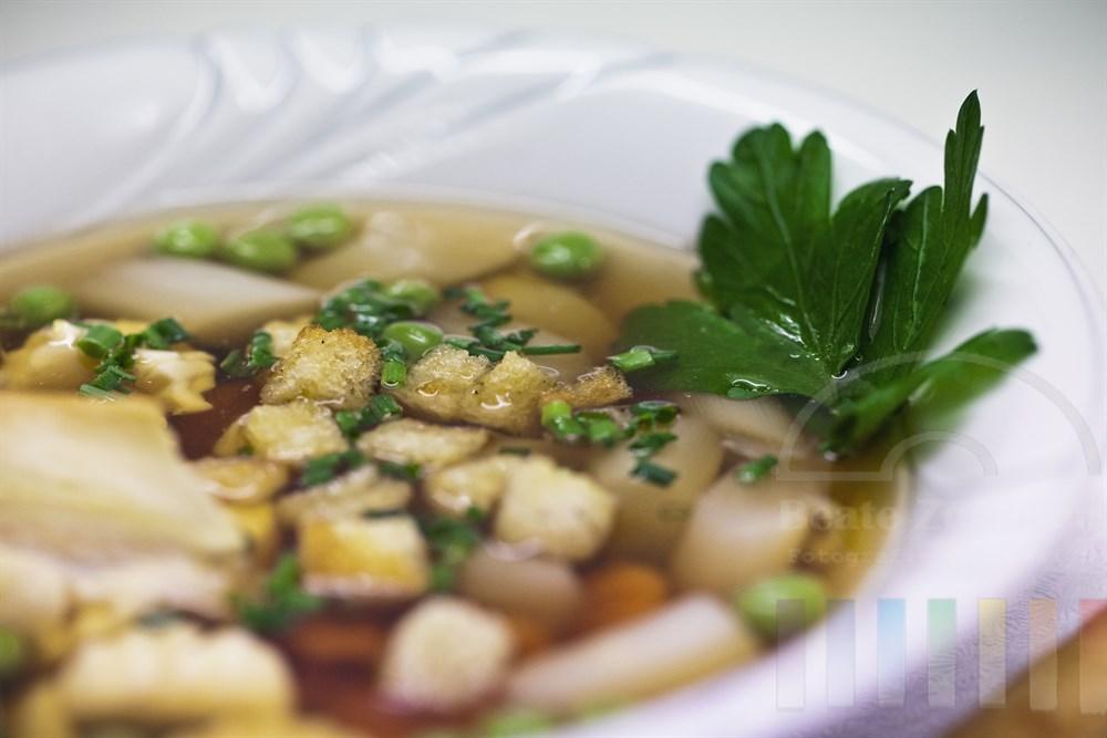 Porzellanteller mit klarer Suppe mit Croutons und Gemuese