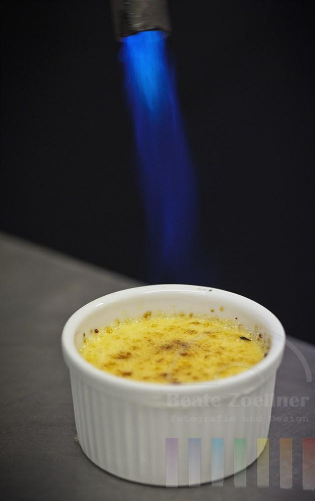 Mit Hilfe eines Brenners wird mit der Flamme die oberste Schicht der suessen Nachspeise Creme Brulee karamellisiert, so dass die typische Kruste entsteht