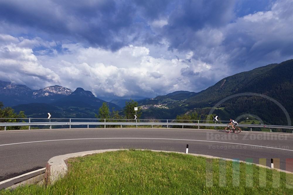 Radsportler faehrt durch Serpentine einen Berg in den Dolomiten (Naehe Bozen) hinauf, sonnig