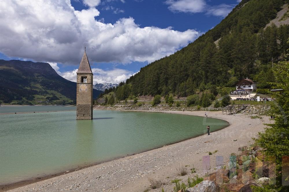 Kirchturm des Dorfes Graun, das bei der Aufstauung des Reschensees (ab 1950) in den Fluten versank, ragt aus dem Reschensee in Südtirol, sonnig