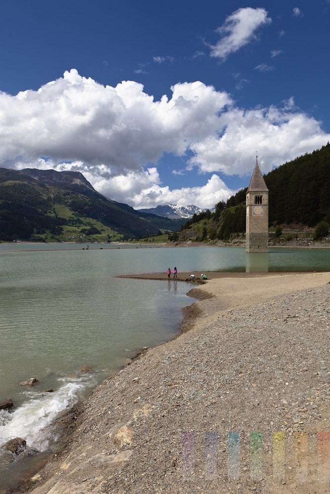 Kirchturm des Dorfes Graun, das bei der Aufstauung des Reschensees (ab 1950) in den Fluten versank, ragt aus dem Reschensee in Südtirol. Am Ufer spielen Kinder, sonnig