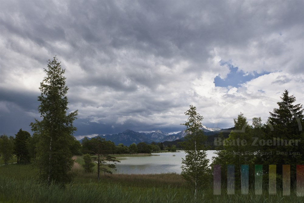 dunkle Gewitterwolken über dem Weissensee bei Füssen im Ostallgäu, im Hintergrund die Alpen