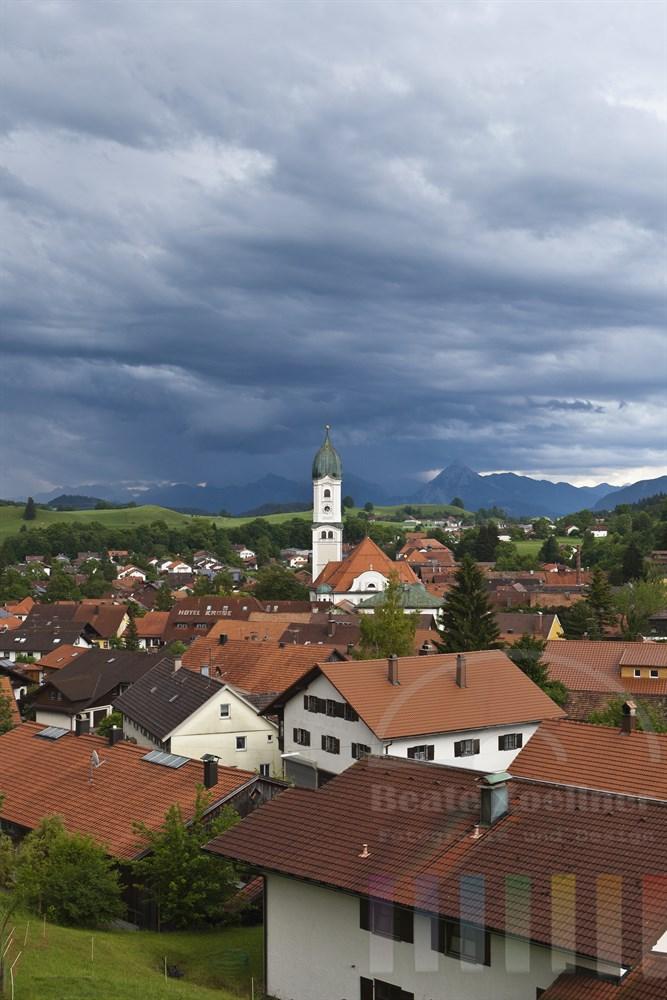Blick ueber die Daecher des Luftkurortes Nesselwang im Allgaeu auf die Alpen, Gewitterhimmel