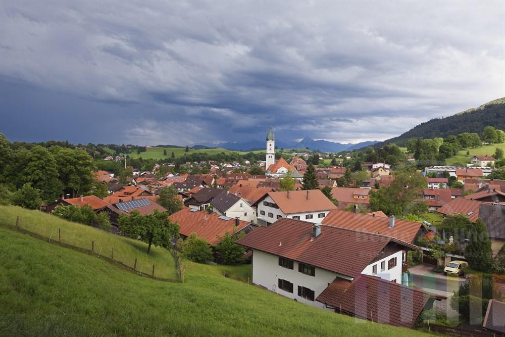 Blick ueber die Daecher des Luftkurortes Nesselwang im Allgaeu auf die Alpen, Gewitter-Himmel